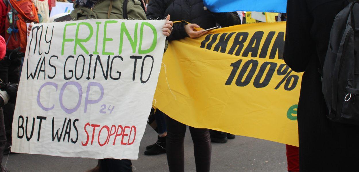 Participante en marcha climática con pancarta que dice que a su colega no lo dejaron entrar a Polonia